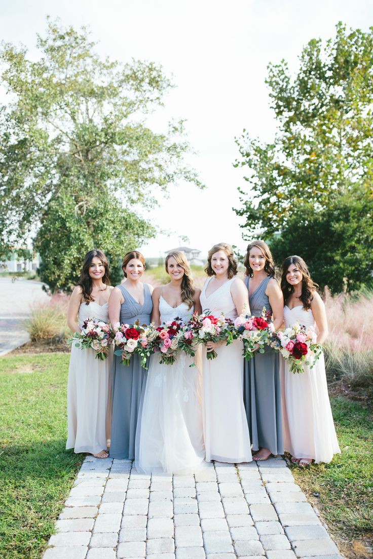 stunning bride and her bridesmaids in shades of pale grey and blush hold loose and lush fall bouquets of red peony, pink garden rose, blush spray rose, pink ranunculus, blue thistle, peach stock, white astilbe, quicksand rose, eucalyptus and vines.