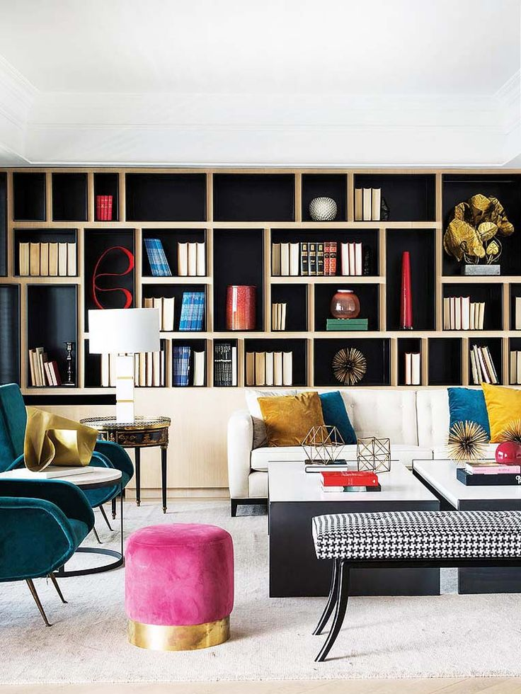 Colorful modern living room with pink ottoman and built-in bookshelves on Thou Swell @thouswellblog