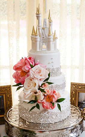 Happily ever after inspired white wedding cake with fresh blooms and a Cinderella Castle cake topper