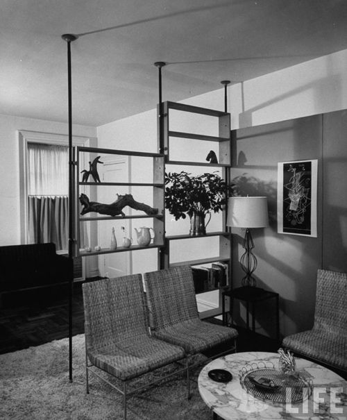 Use floor-to-ceiling pole shelving in a Danish modern inspired home. One of the staples of the '50s and '60s modernist style are free-floating shelves made from teak.