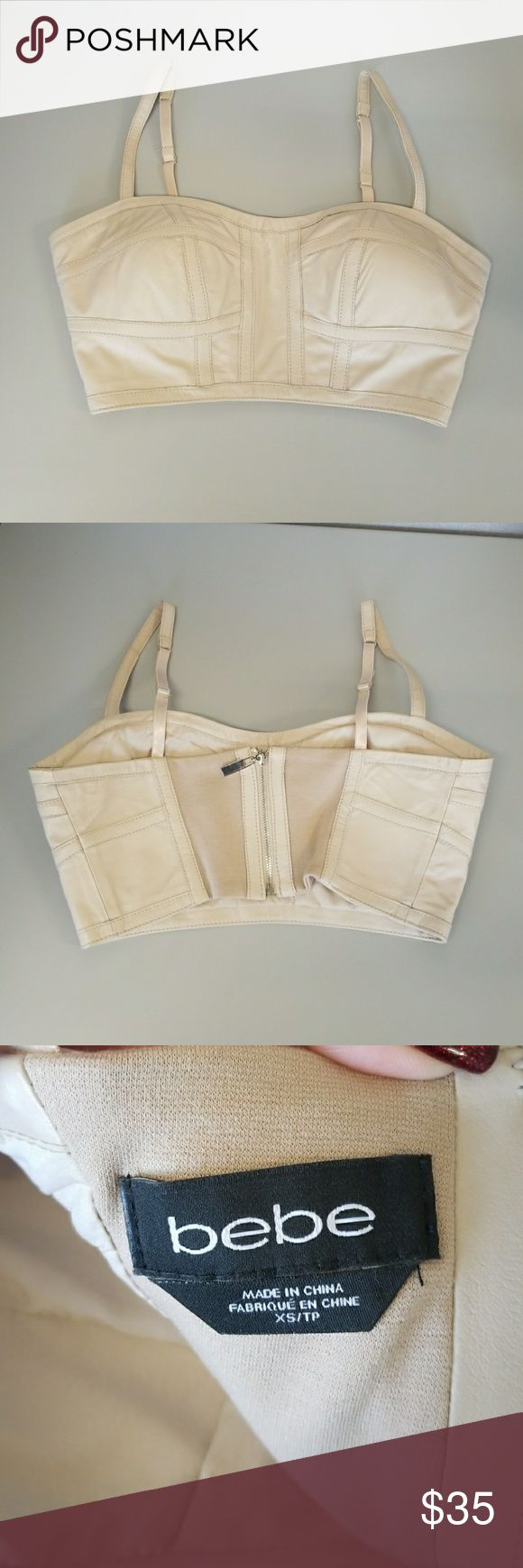 """Bebe Cropped Leather Bustier Size XS COLOR NUDE No flaws. Size XS. Leather his bebe bustier features cropped design, underwire bra and luxe soft leather. Try it with a slew of skirts and high-waisted shorts. 100% leather Center back to hem: 5"""" (13 cm) Spandex lining Adjustable straps Bra cup size B for XXS and XS bebe Tops Crop Tops"""