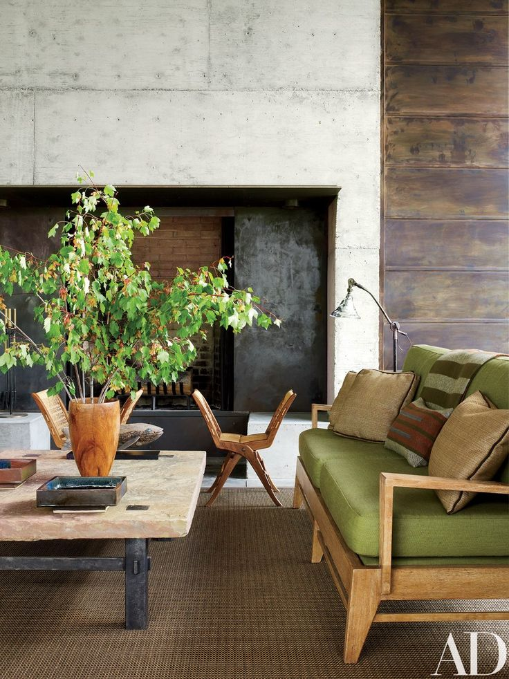 Playing with contrast on the porch, Stuart juxtaposed a stone-top table with a pair of midcentury Italian rope-and-walnut folding stools from Lawson-Fenning. The sofa has seat and back cushions of a Great Outdoors fabric by Holly Hunt; the vintage floor lamp is from JF Chen.