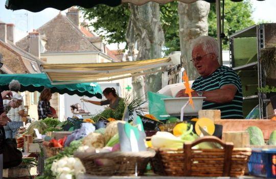 1 Michel Perrusson de Saint-Marcel a l'un des plus grands stands du marché de Buxy.   2 Le marché, ce lieu où se rencontrent touristes et retraités du village…   Photos D.J.