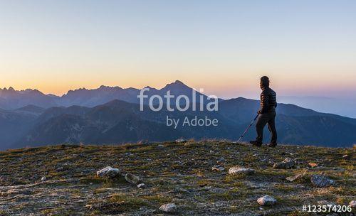 """Pobierz zdjęcie royalty free  """"Tourist  with trekking poles admire the sunrise."""" autorstwa gubernat w najniższej cenie na Fotolia.com. Przeglądaj naszą bazę tanich obrazów online i odnajdź doskonałe zdjęcie stockowe do Twoich projektów reklamowych!"""