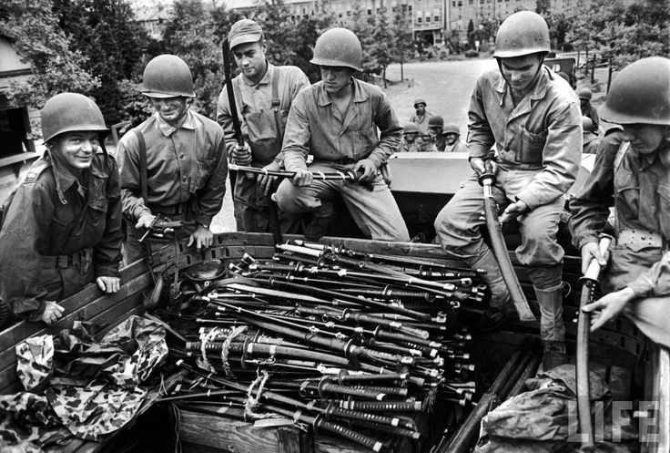 US Marines showing off pile of Japanese swords relinquished by officers of Kurihara Naval base after its surrender to occupying American troops. Location: Onomichi, Honshu, Japan Date taken: September 1945 Photographer: Carl Mydans © Time Inc.