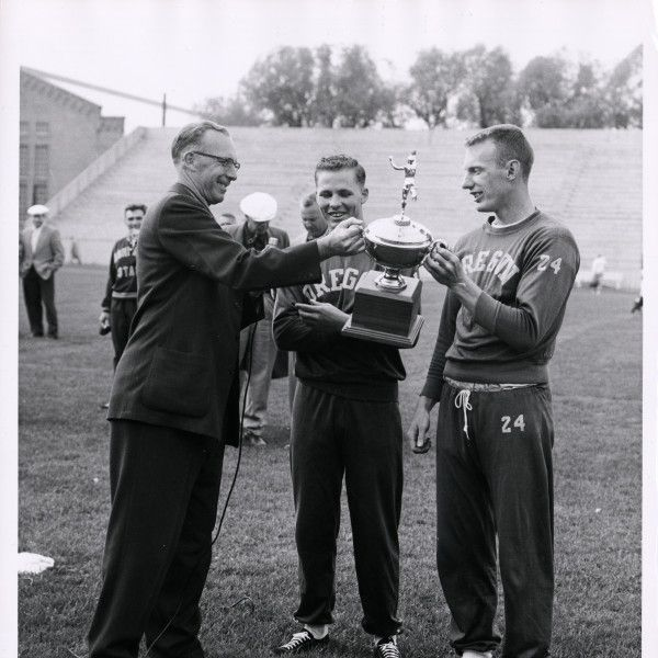Black and white photo of University of Oregon track athletes, Ed Bingham (right) and Martin Pedigo (center) receiving the Edmundson Trophy, presented to the Northern Division track and field champions, by a man identified as Stan Dates. ©University of Oregon Libraries - Special Collections and University Archives