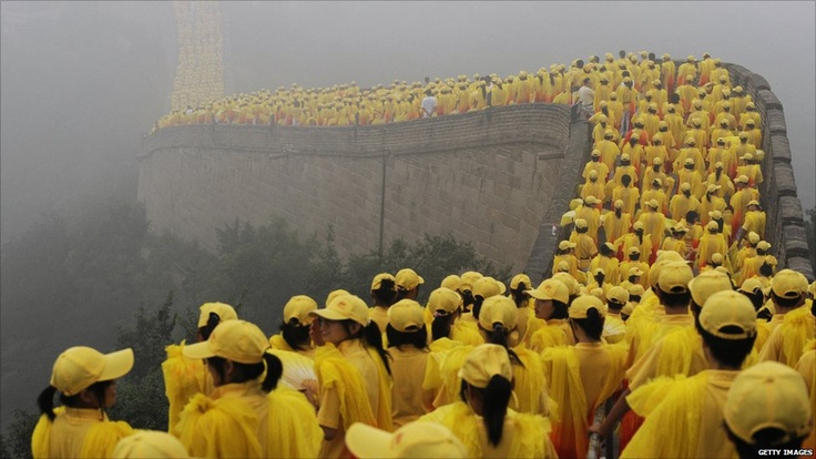 Thousands of volunteers take part in the Olympic torch ceremony, as a section of the Great Wall in Badaling, outside Beijing is shrouded in a haze on August 07, 2008, a day before the Games began