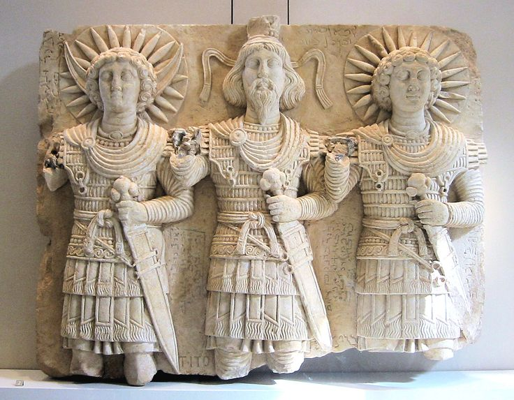 Palmyrean triad : Baalshamin, master of the skies, accompanied on his right by the Moon-god Aglibol and the Sun-god Malakbel (Yarhibol). Cultual relief, limestone, first half of the 1st century AD, found near Bir Wereb, in the Wadi Miyah, on one of the routes to Palmyra. The stele bears religious inscriptions carved by passers-by. H. 60 cm, W. 72 cm, D. 7 cm. Louvre Museum