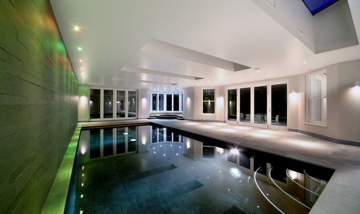 Colour changing downlights highlight this feature wall in a pool room.  Water tight wall lights provide a lower level more peripheral form of light preventing the even lighting effect that would make it feel like a public swimming pool.
