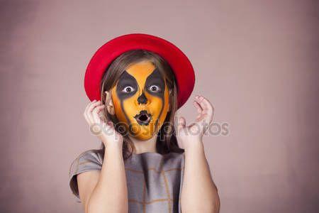 Bella ragazza con la pittura del viso di una zucca — Immagini Stock #127176328