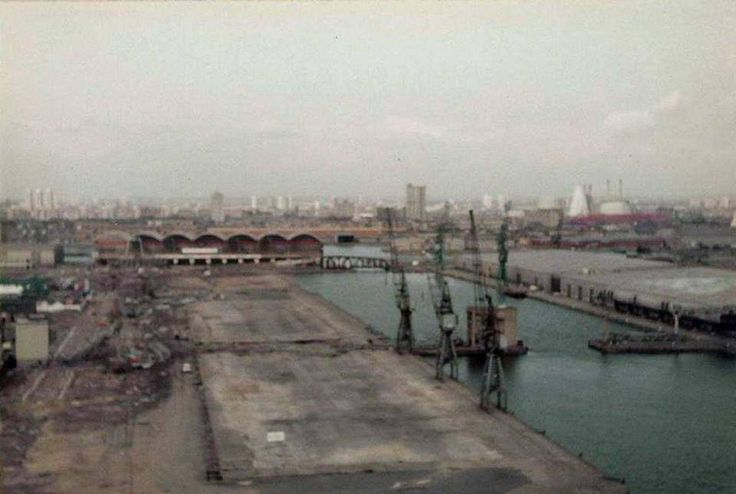 """Millwal Inner Dock, looking north from McDougall's Mill, in 1983. The Glass Bridge is being demolished and the dock, which closed 3 years earlier, lies empty awaiting development. Photo take by Dave Chapman (via """"The Isle of Dogs - Then & Now"""")"""