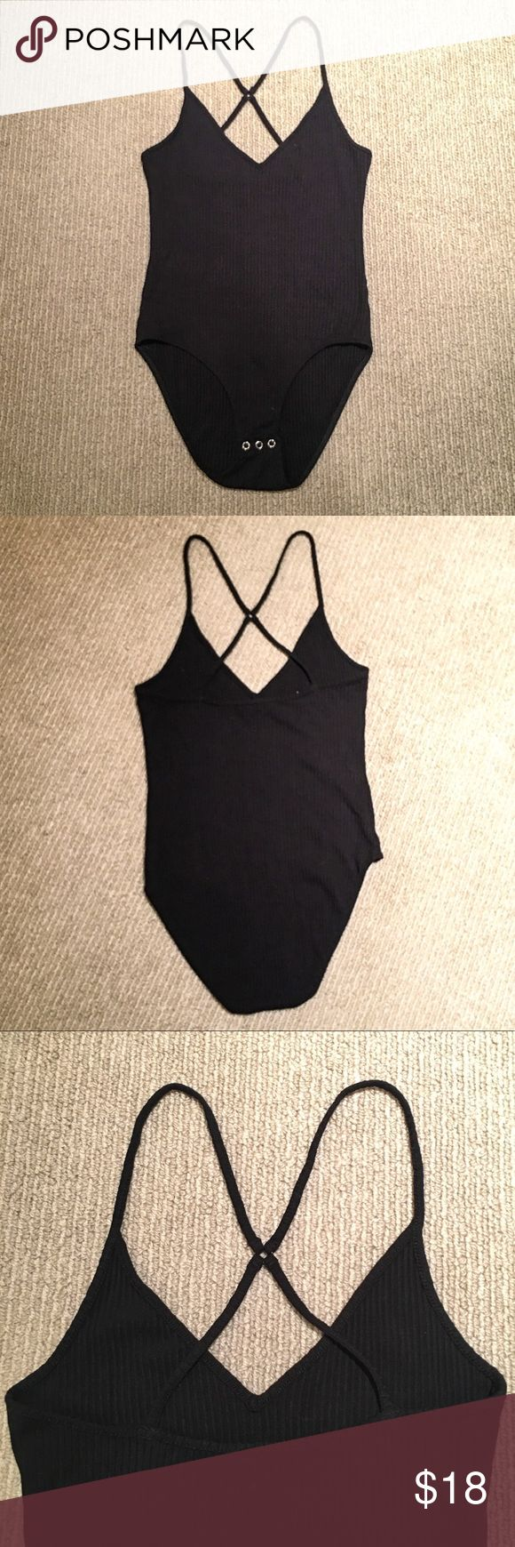 Topshop Black Strappy Bodysuit This black size 8 bodysuit by Topshop has subtle ribbing and comfortably stretchy fabric. It has three silver snaps at the bottom and thin straps that cross in the back. **Never been worn! Topshop Tops Tank Tops