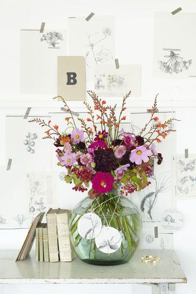 Zo'n kleurrijke bos bloemen steekt prachtig af tegen een achtergrond van botanische prenten in zwart-wit.