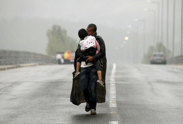 A Syrian refugee kisses his daughter as he walks through a rainstorm towards Greece's border with Macedonia, near the Greek village of Idomeni.