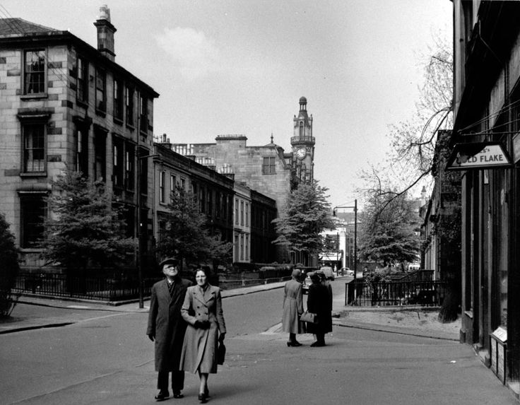 A couple walking in Bank Street in Hillhead, 1955. A group of ladies have stopped for a gossip further along the street, outside a tobacconist's shop. The distinctive tower of Cooper & Co's grocery store and offices is in the distance at the corner of Great Western Road. - TheGlasgowStory