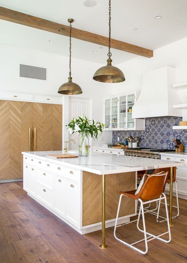 A navy patterened backsplash and hand-scraped oak panels—laid in a chevron pattern over the refrigerator and part of the island—add sophistication to the open kitchen | archdigest.com