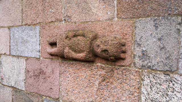 Apparently a crowned person in a long dress, lying down, or at least horizontally carved into the stone, and placed in the church wall. Maabjerg church close to Holstebro approx. 1150-1200. If this person was Jesus, his arms would be out to the sides as nailed to an imaginary cross, as costums were these times. So I think this must be a real life portrait of a dead king, even though I could be mistaken about the crown. It is very symbolic and perhaps not in fact a crown, but something else?