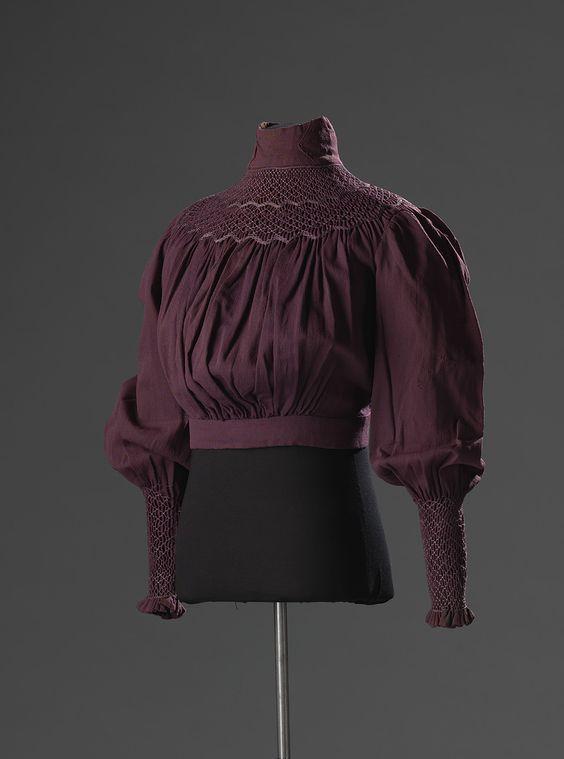 Paarse blouse in de stijl van reformkleding met lange mouwen en smockwerk langs de hals en op de mouwen. De sluiting is middenachter met knopen. De combinatie van blouse en rok was gebruikelijk in deze periode, maar in de reformbeweging werden doorgaans japonnen gedragen.: