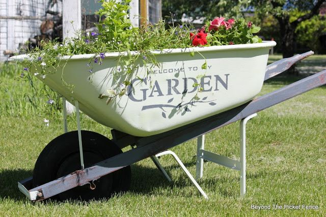 Garden Wheelbarrow planter filled with summer flowers, painted with Tones for Tots Fusion Mineral Paint using Funky Junk's Old Sign Stencils | Beyond the Picket Fence