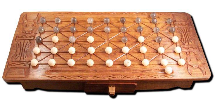 Un plateau de jeu en bois de palissandre avec un petit tiroir. Motif: têtes de zébu. Les pierres utilisées en pions sont des quartz fumé et des calcites orange.