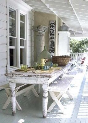 Long weathered white outdoor table with benches on a porch..great space!