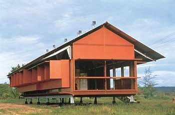 Date: Completed in 1994   Architect: Glenn Murcutt  Location: Yirrkala Community, Eastern Amheim Land, Northern Territory, Australia  Designed for an Aboriginal artist, the Marika-Alderton House ingeniously adapts to the hot, tropical climate of Australia's Northern Territory.    Wide eaves shelter the house from the sun. Pivoting tubes along the roof expel hot air and vertical fins direct cooling breezes into the living spaces.    Because the structure rests on stilts, air circulates…