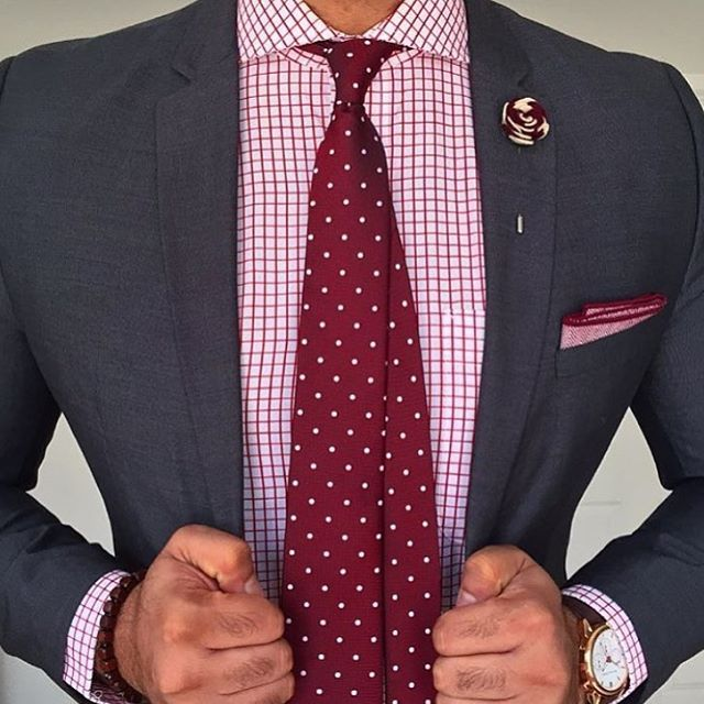 Dark grey suit, white shirt with red check, red tie with white pin dots
