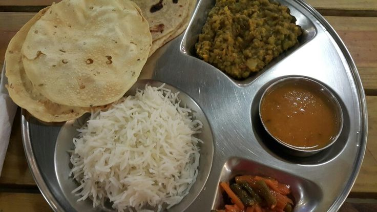 Veg Thali: indian basmati rice; dhaar; kamini s home made pickles; green mug; roti and paapar