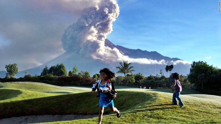 Indonesian girls play at a golf course in Sleman, near Yogyakarta, as a cloud of ash rises from Mount Merapi in the background.