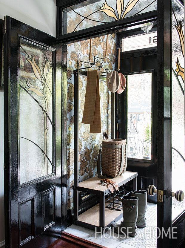 In the entry vestibule of this character-filled home, an industrial hall tree topped with bamboo hat holders adds a functional element to a diminutive space. | Photographer: André Rider | Designer: Richard Ouellette