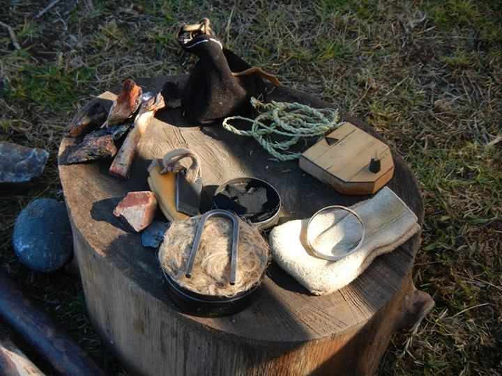 PRIMITIVE TRAIL KIT: In this photo [Bottom center-Clockwise]: Flint & Steel kit with strikers, char cloth; Resin-impregnated Fatwood; Pouch with stones that will throw sparks; handmade Yucca cordage; Ottomani Sun Compass [modified]; selfmade Buckskin pouch with burning lens for firemaking.