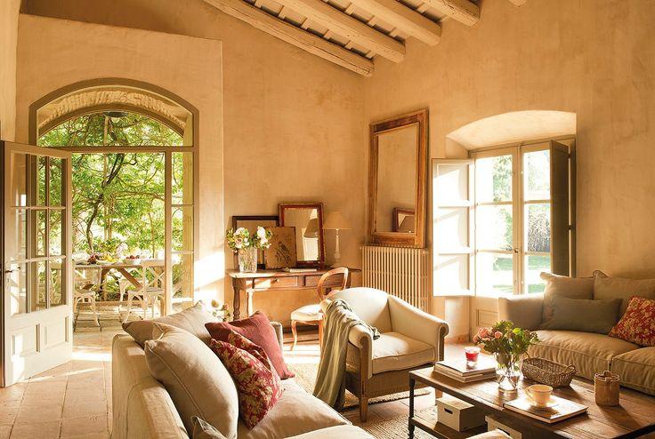 Salón rústico con vigas de mandera pintadas, suelo de toba y sofás clásicos