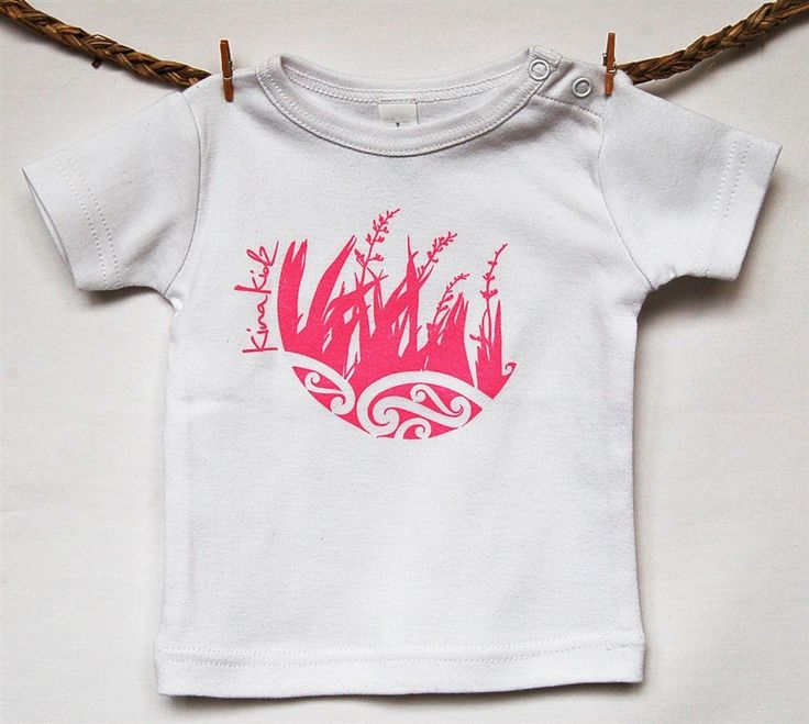 KinaKidz - Organic Wee Tee - Harakeke. The harakeke (flax) plant protects and nurtures each new leaf so it can grow strong and reach its potential. This mirrors our role as parent, caregivers and whanau in nurturing our precious children.  Available in white with a pink design. 160 GSM 100% Organic Cotton - grown without the use of pesticides
