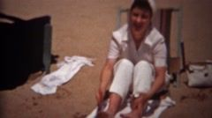 1944: Woman shaking out beach sand from feet seated on canvas chair. TRYON, NC. http://www.pond5.com/stock-footage/60692179?ref=StockFilm keywords:1944, Woman, shaking, beach, sand, feet, seated, canvas, chair, Travel, tourism, tourists, mom, posing, vacation, sandy, sunbathing, relaxing, modest, lounge chair, cleaning, beautiful, pacific, coast, uptight, mean, unhappy, annoyed, dirty, 1940s, 8mm, film, old, vintage, unique, archival, Americana, documentary, tv, news, commercial, history…