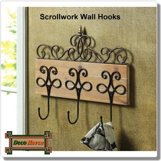 Scrollwork Wall Hooks - These decorative wall hooks make organization beautiful! Three metal hooks topped with scrolling metalwork and finished with a gleaming finial create the perfect organization station for your entry way, hall and beyond. Rustic wooden base.