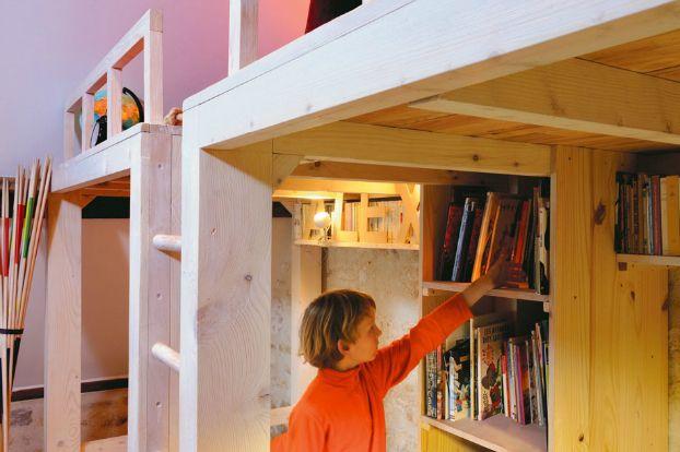 За лестницей от пола до потолка расположены емкие стеллажи для книг.  (кровать-лофт,двухъярусная кровать,детская кровать,детская,игровая,детская комната,детская спальня,дизайн детской,интерьер детской,индустриальный,лофт,винтаж,стиль лофт,индустриальный стиль,архитектура,дизайн,экстерьер,интерьер,дизайн интерьера,мебель) .