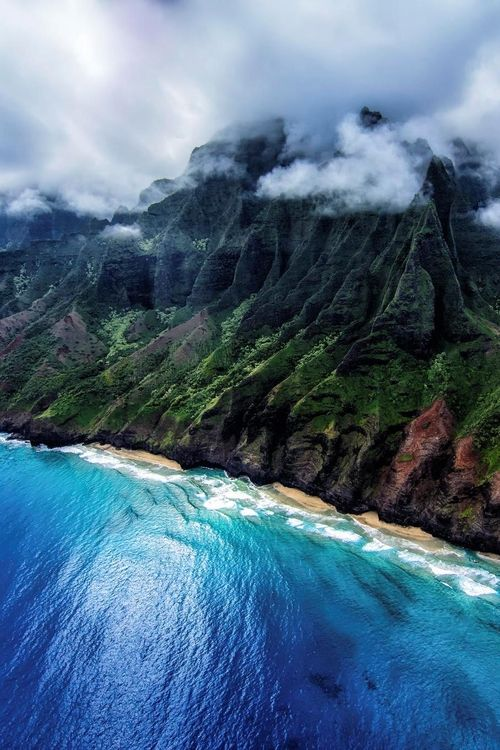 Na Pali Coast, Kauai, Hawaii. Taken from an open door helicopter. The clouds began to break as we were headed back inland.