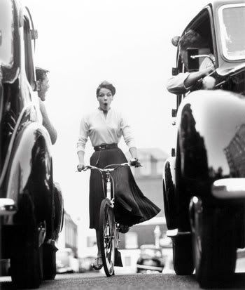 50s. Love the expression and the fact she's bicycling in traffic in a tailored skirt and blouse!