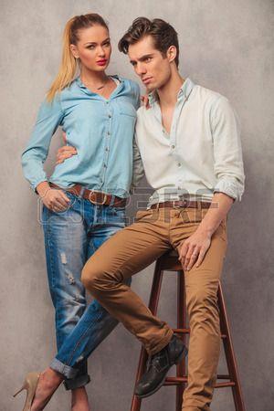 couple posing in studio, man seated embracing girlfriend while looking away