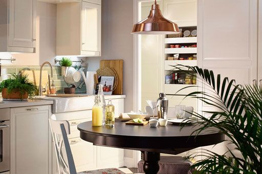 Close-up of a wooden white kitchen with a grey stractor fan, a cooper ceiling lamp and a black kitchen round table