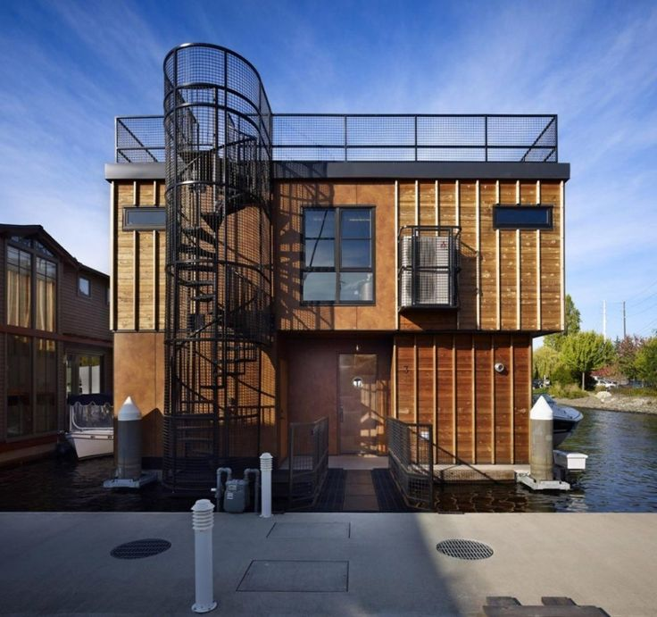 Задний фасад дома, индустриального вида винтовая лестница на террасу на крыше дома. .