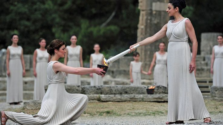 Women dressed as vestal virgins acted as guardians of the flame during the lighting ceremony. The specially-made torch was used to transfer the flame to the archaic pot, which was taken via an ancient pathway to the site of the first Olympic Games. ~ BBC