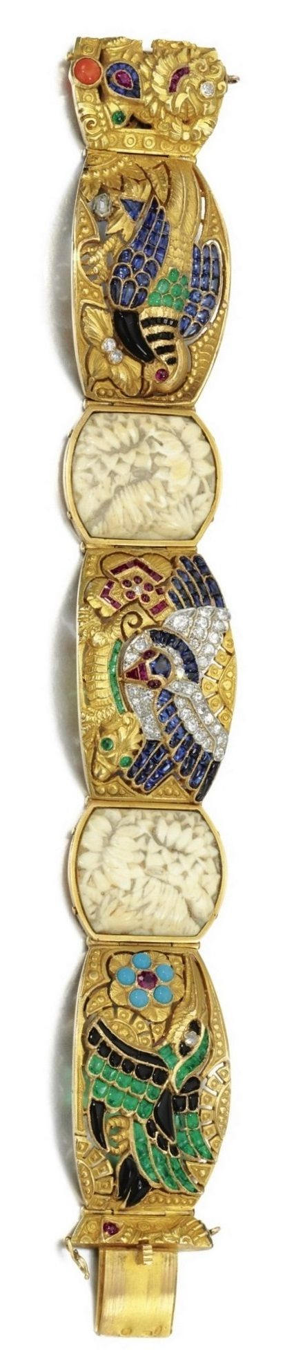 AN ART DECO GOLD, GEM-SET AND DIAMOND BRACELET, SPANISH, CIRCA 1930. Designed as a series of tonneau-shaped curved plaques, depicting birds in flight, a lizard and Aztec inspired deity, set with calibré-cut and buff top sapphires, emeralds, rubies, coral, turquoise, onyx and accented with variously cut diamonds, to pierced and engraved backgrounds of foliate and organic motifs and two carved bone plaques, French import mark and Spanish assay mark. #ArtDeco #bracelet