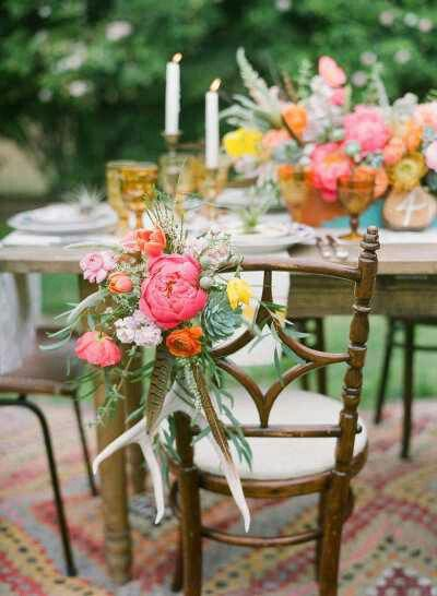 Like this composition of flowers, antlers, pheasant feathers—not as chair décor, but as a centerpiece.