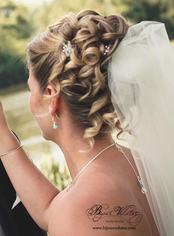 Bijou de dos mariage : pendentif de dos original bleu turquoise, magnifique coiffure de mariée avec chignon bouclé et voile de mariée en tulle ivoire.