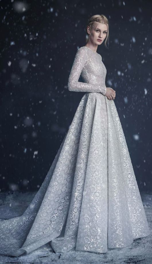 Glamorous long-sleeve metallic detail winter wedding dress; Featured Dress: Paolo Sebastian
