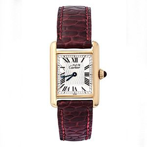 This beautiful ladies Must de Cartier watch features a yellow gold gold case, beautiful roman numerals and deep blue reflective hands that contrast with the ornate ruby and gold crown. The watch's strap is textured maroon coloured leather. #cartier #vintagewatch