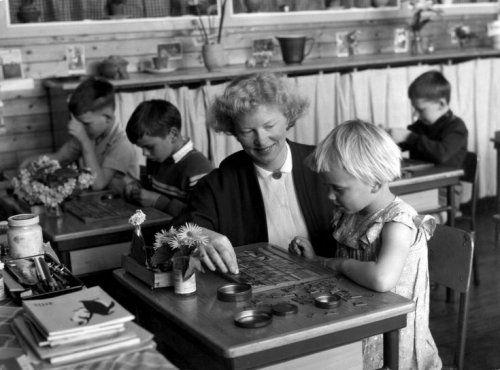 De juf helpt een schoolmeisje aan haar tafeltje in het schoollokaal met haar leesplankje (aap noot mies), 1958.