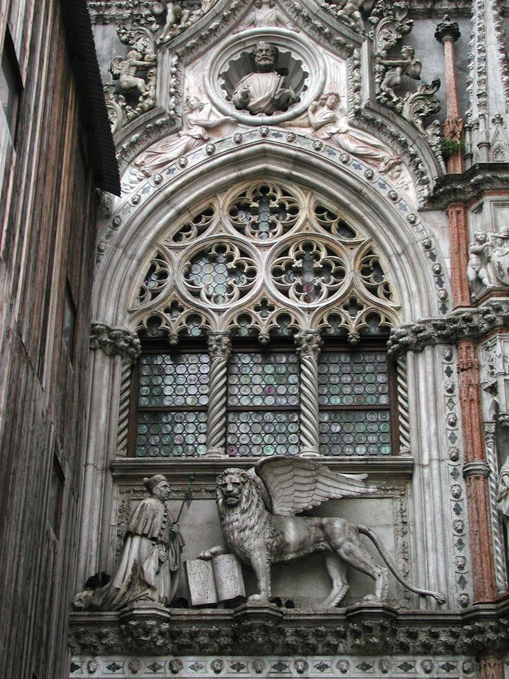 Porta della Carta - St. Mark Sculpture -- Doges' Palace, Venice, Italy - The beautiful Gothic arched entryway was built between 1438 and 1442, designed by Bartolomeo and Giovanni Bon.     St. Mark appears prominently in the roundel in the Porta della Carta. As the patron saint of Venice he or his symbol, the lion, is visible in almost every civil sculpture in the city.