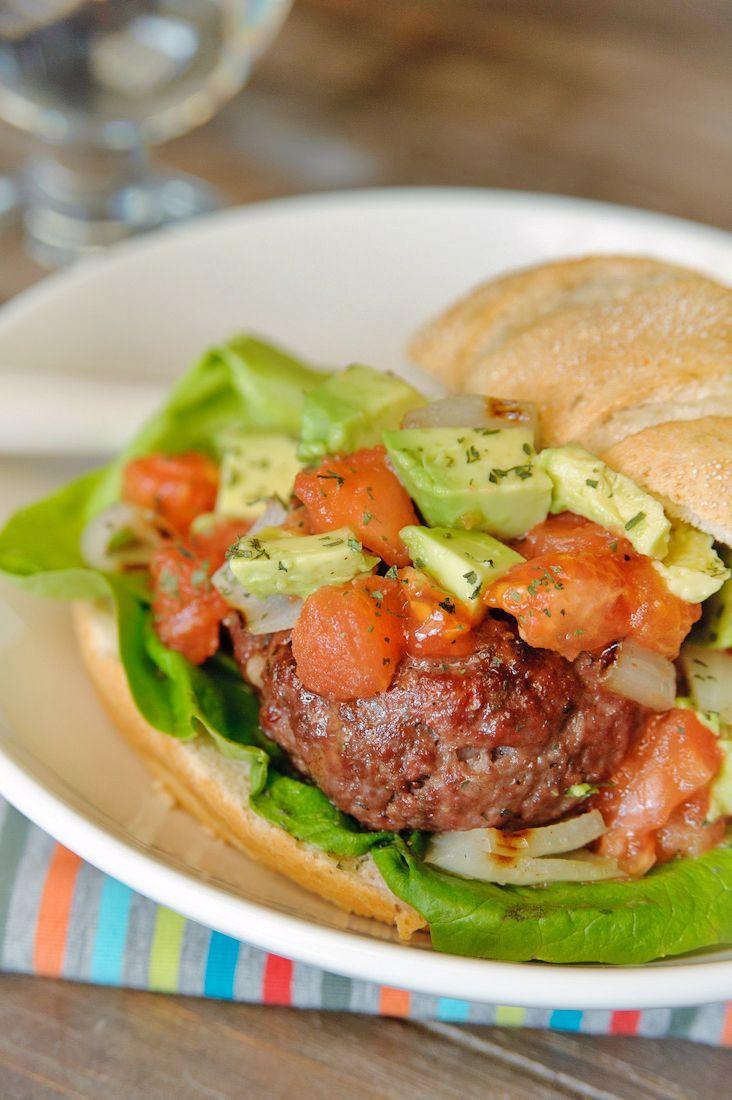 Bereiden:Meng de kruiden en kneed door het gehakt. Verdeel het gehakt in 4 gelijke stukken, leg een plak mozzarella in het midden en vouw het gehakt erom heen. Vorm hier stevige hamburgers van. Doe de tomaten in een kom, besprenkel met wat olijfolie en breng op smaak met grof zeezout en versgemalen peper. Verwarm de oven voor op 175°C. Grill de hamburgers in een hete pan enkele minuten aan elke kant. Breng over naar de oven en laat nog 15 minuten verder garen. Grill de ui en tomaten langs...